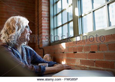 Malinconici donna di bere il caffè nella caffetteria Foto Stock