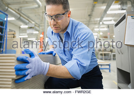 Lavoratore esame di assi di legno in fabbrica Foto Stock