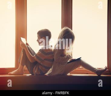 Due bambini sono seduti dalla finestra a casa giocando sulla loro tecnologia compresse con giochi e app per un intrattenimento conce Foto Stock