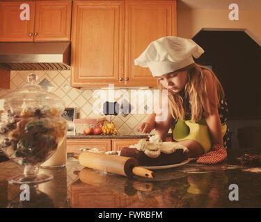 Un bambino è la glassa di una torta in cucina per una panetteria, la dieta o il concetto di cibo. La bambina indossa Foto Stock