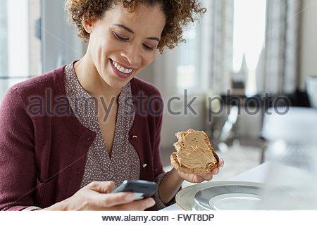 Donna texting mentre si consuma la prima colazione. Foto Stock