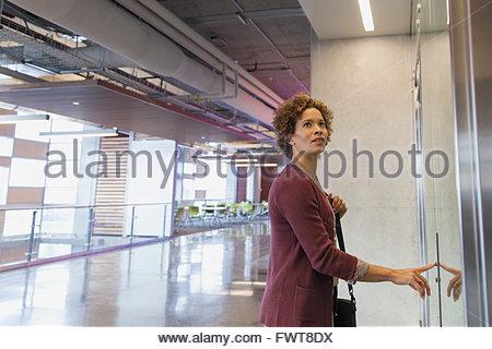 Donna spingendo il pulsante su ascensore presso l'ufficio. Foto Stock