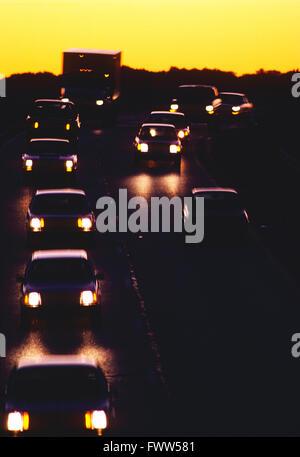 I fari anteriori quando si incrociano altri del traffico autostradale contro il tramonto Foto Stock
