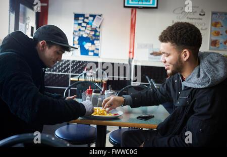 Due gli studenti di sesso maschile di mangiare pasti in Café Foto Stock