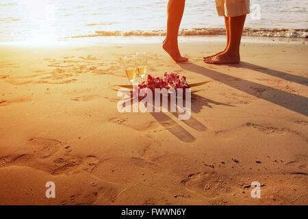 Matrimonio sulla spiaggia a piedi di coppia romantica e due bicchieri di champagne al tramonto