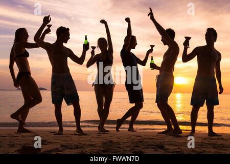 Beach party, gruppo di giovani a ballare, amici di bere birra e cocktail al tramonto Foto Stock