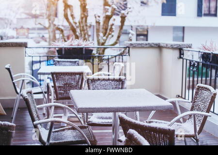 Terrazza del caffè strada in inverno, tavoli e sedie coperte da neve Foto Stock