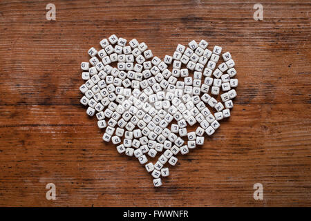 Il cuore da lettere sullo sfondo di legno, amore apprendimento, educazione e concetto di alfabetizzazione Foto Stock