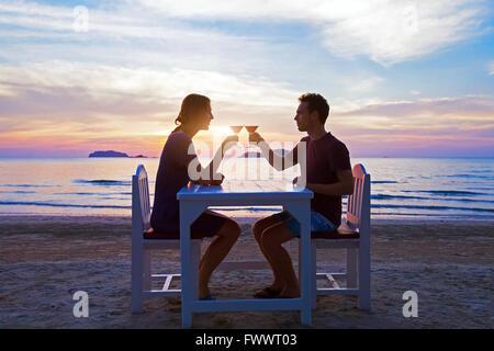 Cena romantica a lume di candela sulla spiaggia nel ristorante di lusso, coppia in luna di miele a bere cocktail tropicali al tramonto Foto Stock