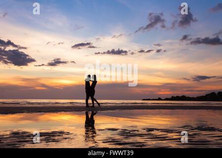 Silhouette di coppia sulla spiaggia al tramonto, bello sfondo su amore e relazioni, uomo e donna Foto Stock