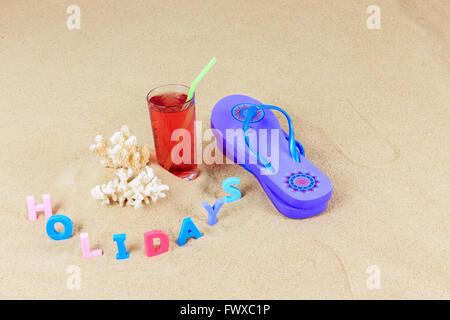 Coppia di blu flip flop con pezzi di corallo, bevanda a base di frutta in vetro con paglia e lettere colorate ortografia Foto Stock