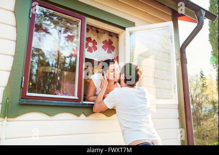 La Svezia, Gastrikland, Sandviken, giovane baciare anche se una finestra di casa Foto Stock