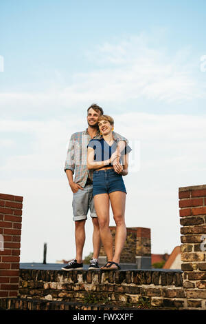 Germania Berlino, Smiley coppia giovane in piedi sul tetto Foto Stock
