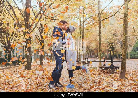 Autunno kiss, giovane coppia amorevole nel parco con foglie che cadono Foto Stock