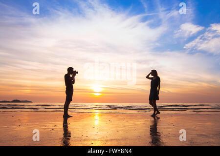 Fotografo e modello, spiaggia di ripresa fotografica al tramonto, l'uomo a scattare foto di donna Foto Stock