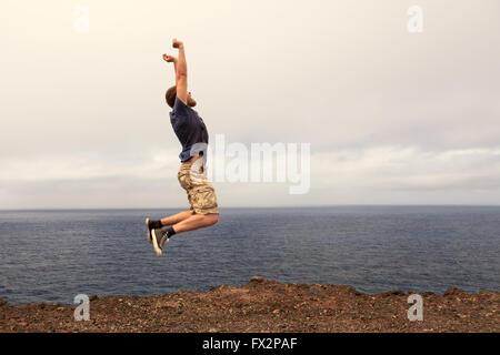 Il successo o il concetto di win - uomo gioioso jumping outdoor Foto Stock