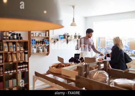 Maschio assistente di vendita che serve i clienti di sesso femminile nel negozio di specialità gastronomiche Foto Stock