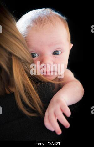 Un neonato boy guarda la fotocamera mentre annidato nella sua madre capelli contro uno sfondo nero Foto Stock