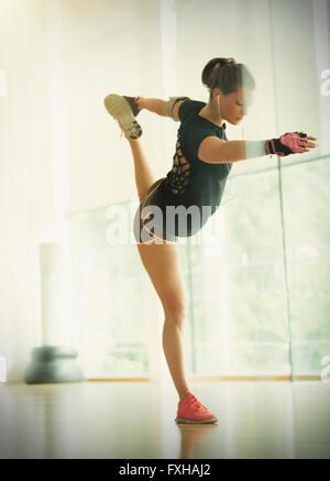 Donna che mantiene re posizione del signore della danza in palestra studio Foto Stock