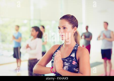 Focalizzato donna con le mani in posizione di preghiera nella classe di yoga Foto Stock