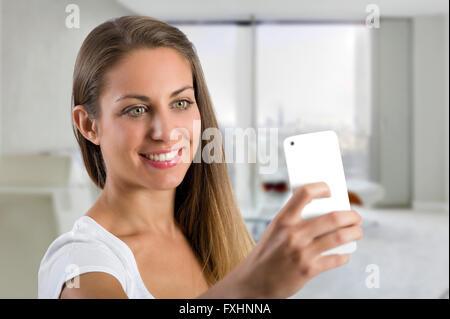 Single carino donna sorridente prendendo un selfie in ufficio con smart phone fotocamera in mano vicino al suo volto Foto Stock