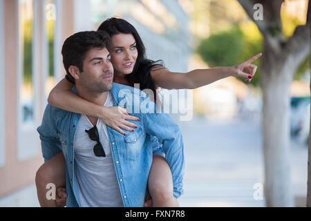 Coppia felice in vacanza o in vacanza dando piggyback Foto Stock