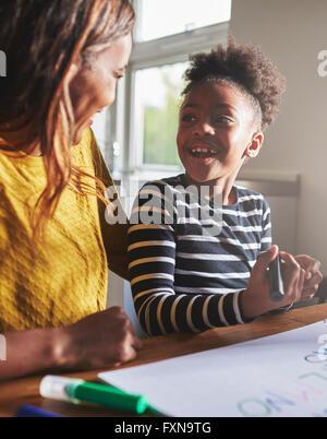 Bambino felice imparare l'alfabeto con sua madre, nero donna e bambino Foto Stock