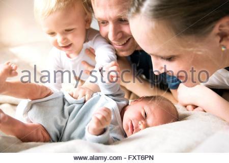 Madre, padre e figlio guardando in giù a baby boy sorridente Foto Stock