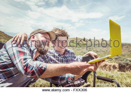Uomo e figlio adolescente seduto in campeggio sedie tenendo selfie laptop, Bridger, Montana, USA Foto Stock