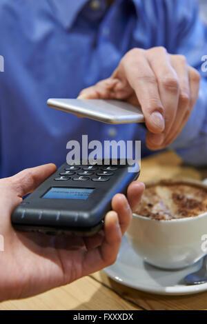 Uomo che utilizza il pagamento senza contatto App sul telefono cellulare in Cafe Foto Stock