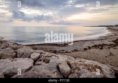 Una lunga esposizione foto di un Seawall in spiaggia al tramonto Foto Stock