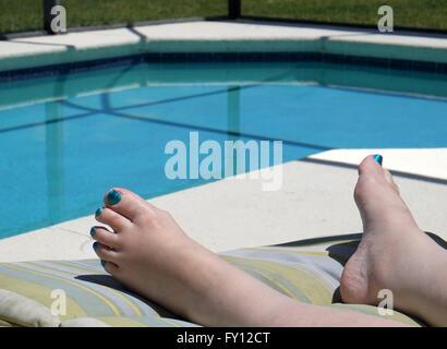 I piedi di una donna matura che indossa lo smalto per unghie sulle sue dita per far corrispondere la piscina colore. Foto Stock
