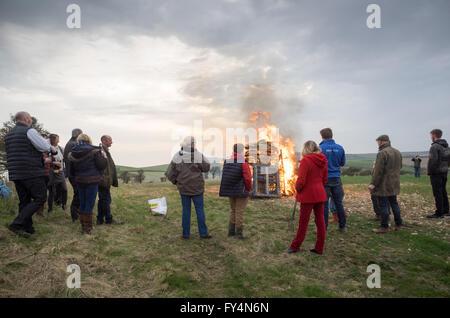 Un gruppo di spettatori a guardare in piedi intorno ad un fuoco acceso beacon per la regina il novantesimo compleanno Foto Stock