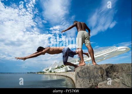RIO DE JANEIRO - Febbraio 25, 2016: i giovani brasiliani salto nella baia di Guanabara dalla parete di fronte al Museo di domani. Foto Stock