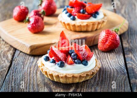Dessert di frutta crostate con crema, fragola e mirtillo su un tavolo di legno Foto Stock
