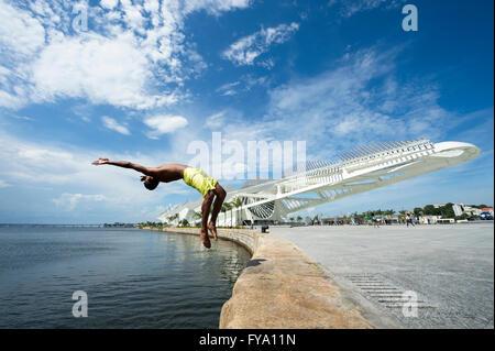 RIO DE JANEIRO - Febbraio 25, 2016: giovane brasiliano salta nella baia di Guanabara davanti il recentemente completato il museo di domani. Foto Stock