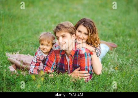 La famiglia felice in un parco di erba Foto Stock
