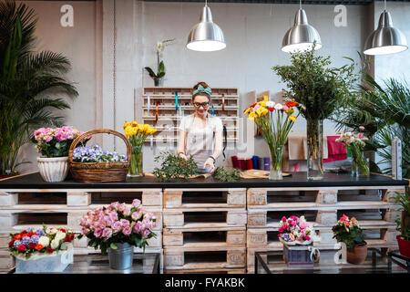 Sorridente attraente giovane donna fioraio permanente e a lavorare nel negozio di fiori Foto Stock