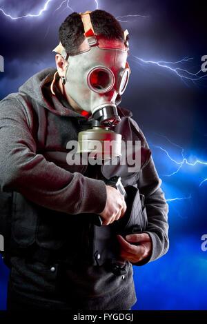 Uomo con lunga giacca di pelle e il fucile di assalto su sfondo tempesta Foto Stock