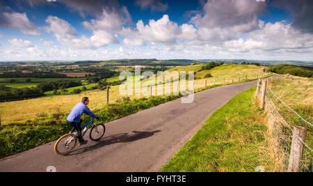 Un ciclista su una tranquilla strada di campagna sulla cima di una collina, Bulbarrow, nel Dorset Downs nel sud Foto Stock