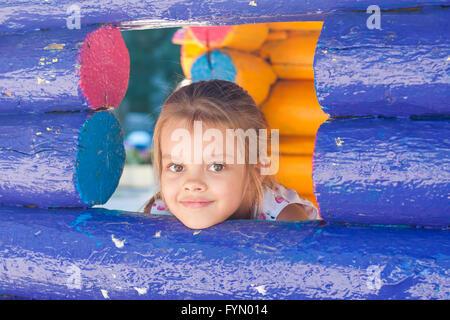 Cinque anni di bambina guarda fuori da una finestra in legno Foto Stock