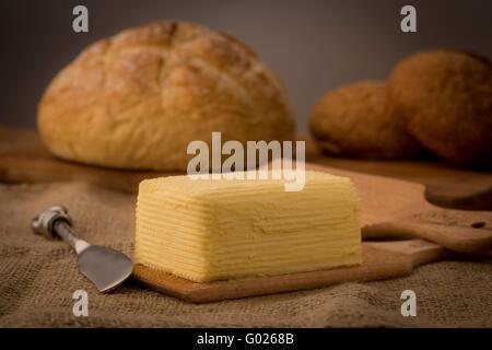 Mano agitati in casa il burro sulle pale in legno con Coltello per burro e la pagnotta di pane. Foto Stock