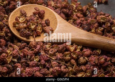 Cucchiaio di legno in grani di pepe Szechuan ardesia sul bordo di taglio Foto Stock