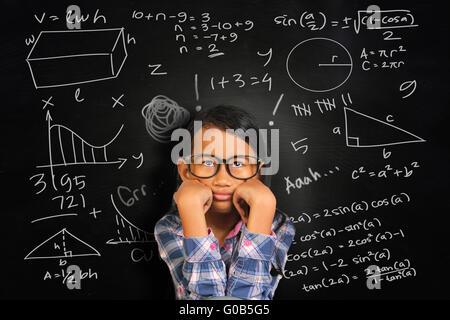 Piccolo studente asiatica ragazza con gli occhiali che mostra annoiato e stanco sulla lavagna verde con math equivalenti Foto Stock