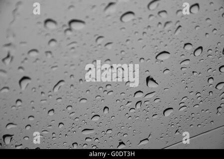 Gocce d'acqua o gocce di pioggia su una superficie di vetro (messa a fuoco selettiva) Foto Stock