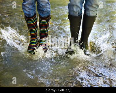 Coppia felice indossando variopinti stivali da pioggia Foto Stock
