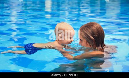 Felice piccolo sport uomo ha lezione di nuoto con la madre - attivo baby nuotare con il divertimento nelle mani Foto Stock