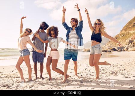 Ritratto di entusiasti giovani amici permanente sulla spiaggia. Gruppo multirazziale di amici godendo una giornata Foto Stock