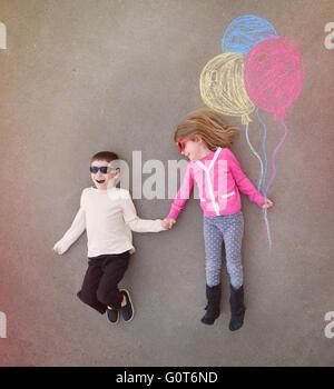 I bambini sono tenendo le mani al di fuori con colorati chalk palloncini delineato sul cemento per un creativo, artigianali o il concetto di riproduzione Foto Stock