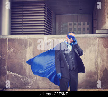 Un uomo di affari è vestito come un super eroe utilizzando un telefono in città per un unico umoristico o il concetto di comunicazione. Foto Stock